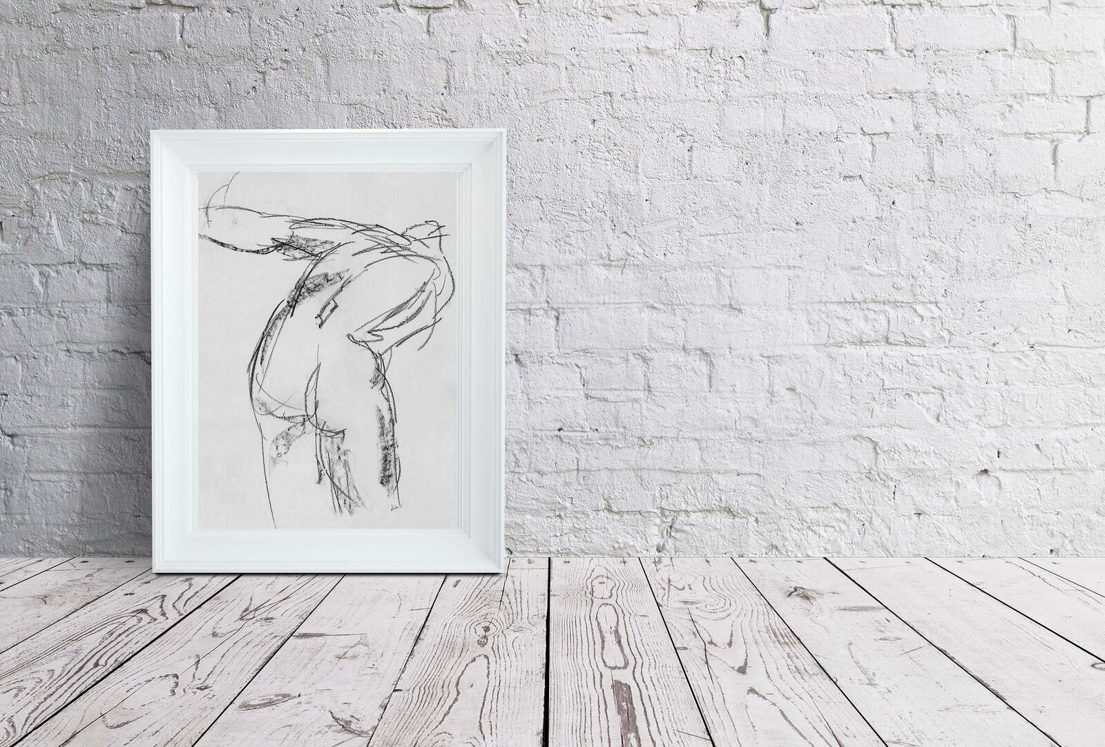 Charcoal female figure sketch framed and sitting on distressed wood floor leaning on a white brick wall