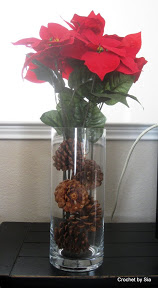 Poinsettias in glass vase filled with pinecones