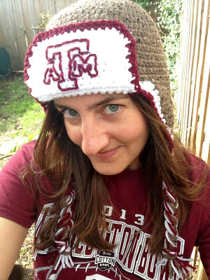 Me wearing an ear flap hat with the Texas A&M logo embroidered on the front
